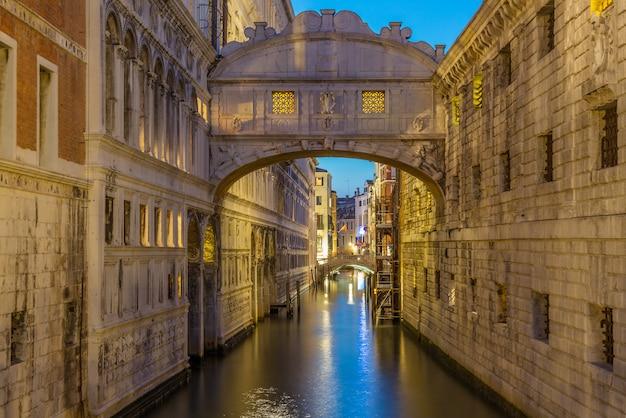 Мост вздохов ponte dei sospiri загорелась на голубом часе ночи захода солнца в венеции, италии. известная достопримечательность.