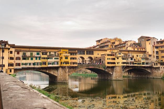 Понте веккьо над рекой арно во флоренции, италия.