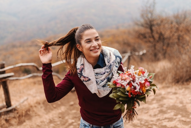 Красивая усмехаясь девушка при ponytail держа букет пока стоящ на glade во времени осени.