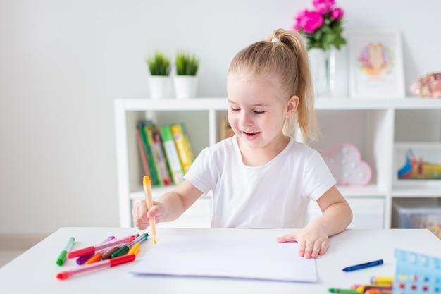 Белокурая счастливая маленькая девочка с ponytale рисуя и писать lsitting белым столом в свете roon. дошкольное образование, раннее обучение