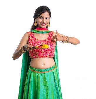 Красивая индийская молодая женщина держа pooja thali или выполняя поклонение на белой стене
