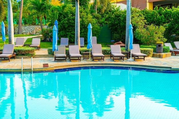 Шезлонги и зонтик вокруг бассейна с кокосовой пальмой