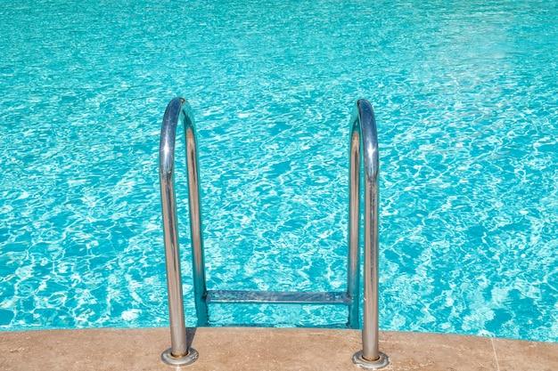 Вход в бассейн. перила лестницы спускаются к бассейну.