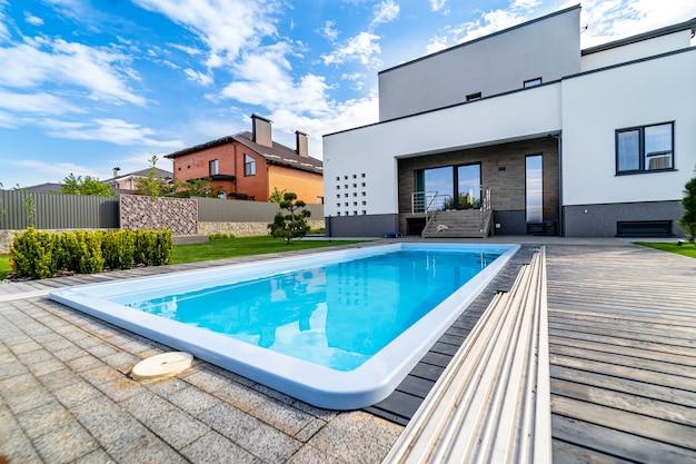 호화로운 집에 있는 수영장. 깨끗한 물. 바닥에서 볼 수 있습니다. 오픈 베란다와 차고가 있는 최신식 주택. 현대 건축입니다.