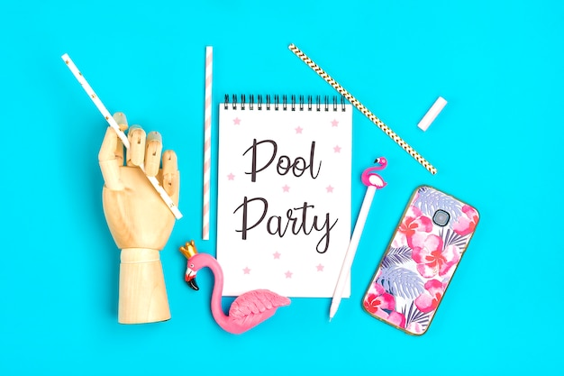 Pool party notebook, pen, flamingo figure, smartphone, wooden hand hold drinking paper straws on blue background