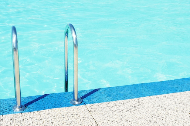 Pool side, blue pool water and metal ladder handrails.