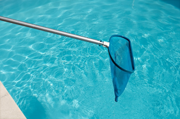 Pool skimmer on bright water surface in swimming pool