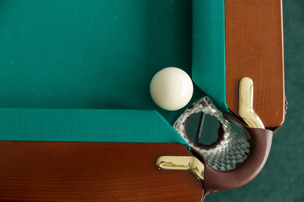 A pool table. top view. the ball rolls into the pocket. greencloth