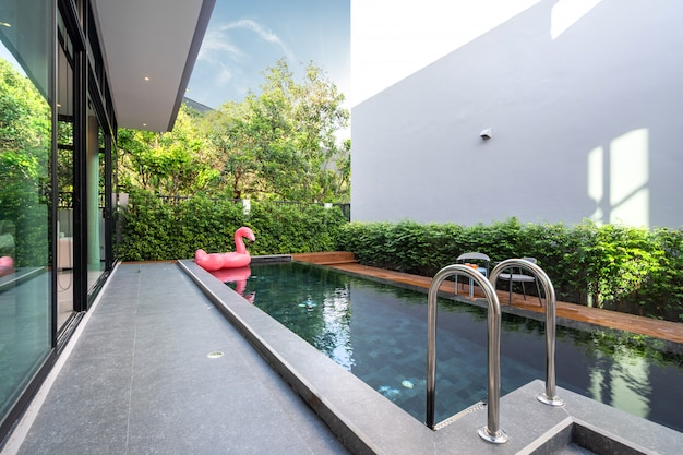 Pool terrace and pink floating duck in infinity swimming pool