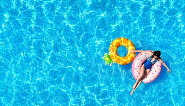 Текстура воды в бассейне с женщиной на надувных водных игрушках