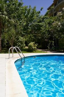 녹지를 배경으로 집 안뜰에 푸른 물이 있는 수영장