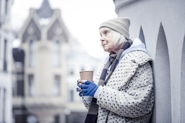 貧しい乞食。お金を物乞いしながら建物の隅に立っている悲しい高齢女性