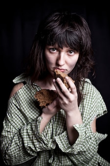 Poor beggar woman with a piece of bread.