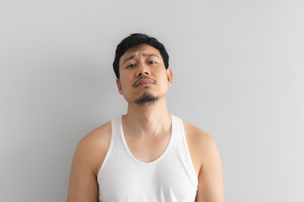 Poor and depressed man wear white tank top on grey background.