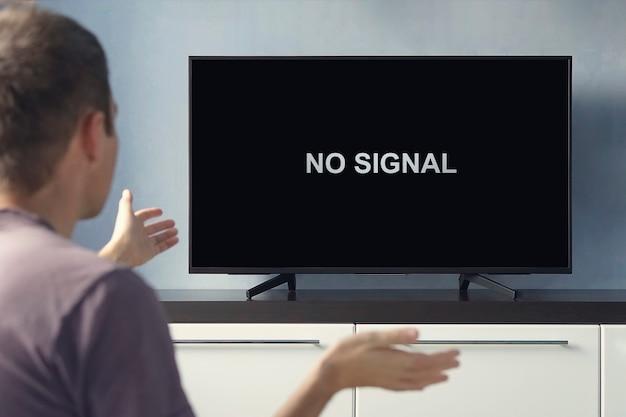 Плохой сигнал цифрового тв. нет сигнальной надписи на экране телевизора. парень расстроен из-за поломки телевизора.