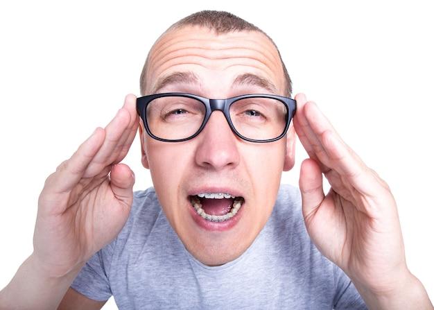 가난한 시력 개념 - 흰색 배경에 격리된 치아에 교정기가 달린 안경을 쓴 재미있는 청년