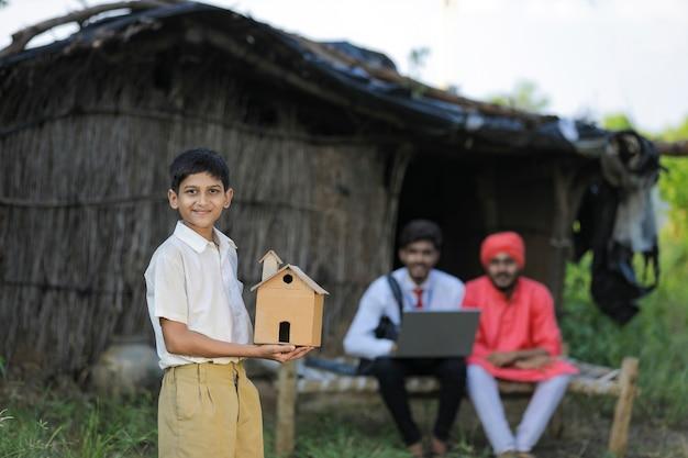 Poor farmer little child holding handmade home in hand