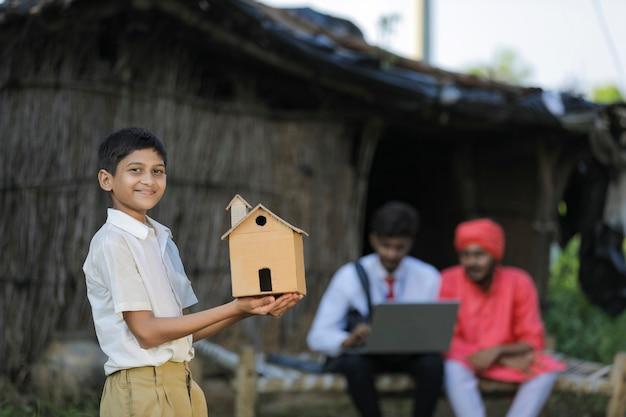 手作りの家を手に持っている貧しい農夫の小さな子供
