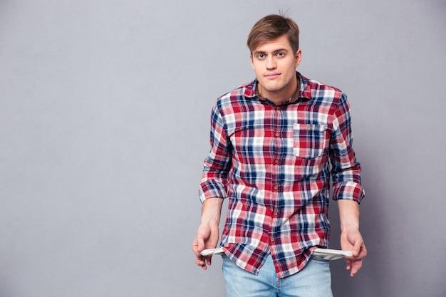 Бедный красивый молодой человек в клетчатой рубашке и джинсах показывает пустые карманы над серой стеной