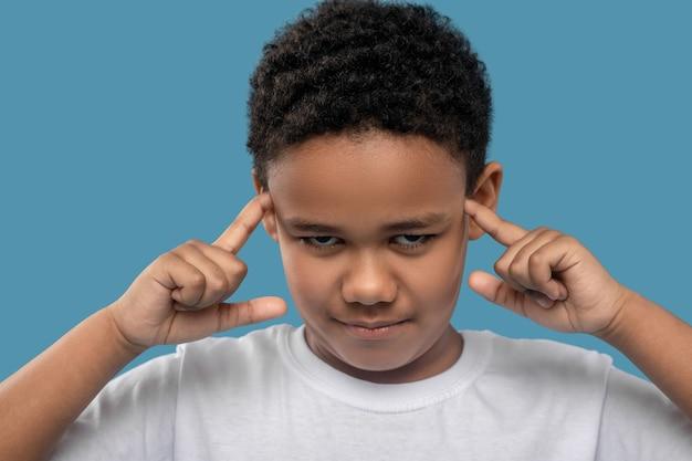 건강하지 않은. 파란색 배경에 머리 근처에 손가락을 들고 나쁜 느낌 아프리카 계 미국인 소년의 슬픈 얼굴