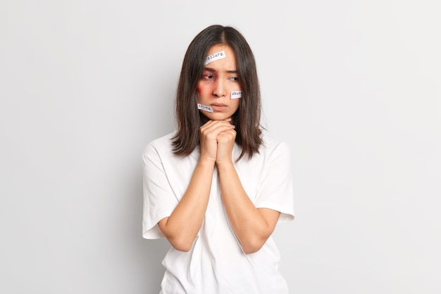 Poor helpless woman looks thoughtfully down has bruises on face becomes victim of killer suffered severe sadistic torture has family problems with husband dressed in whitte t shirt. depression despair