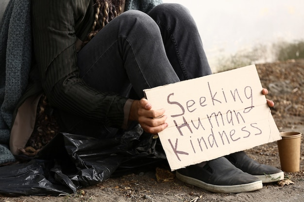 Бедный бездомный держит картон с текстом в поисках человеческого добра на открытом воздухе