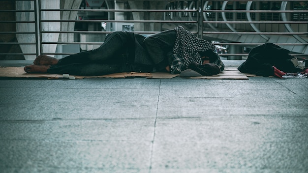 Poor homeless man or refugee sleeping on the floor of public path way in the city