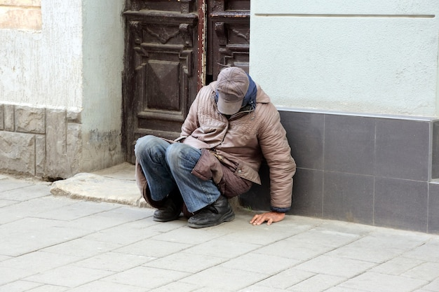 Poor homeless man sitting near the wall of the building