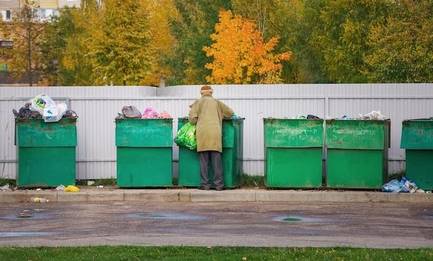 가을에 쓰레기를 검색하는 가난한 노숙자 노인. 쓰레기통을 뒤지는 남자
