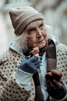 Poor and hungry. nice aged woman thinking about her life while holding a piece of bread