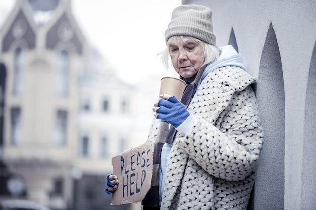 貧しい生活。お金を物乞いしながらプラスチックカップで立っている不幸なホームレスの女性