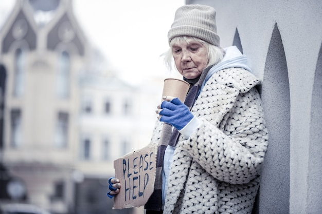 Poor life. unhappy homeless woman standing with a plastic cup while begging people for money