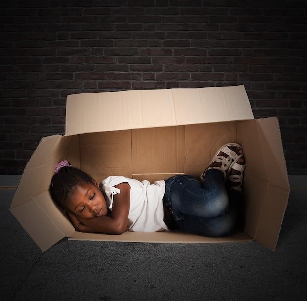 Poor little girl sleeps in a cardboard