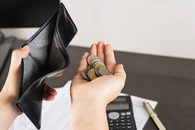 Poor man hand open empty wallet and holding coins