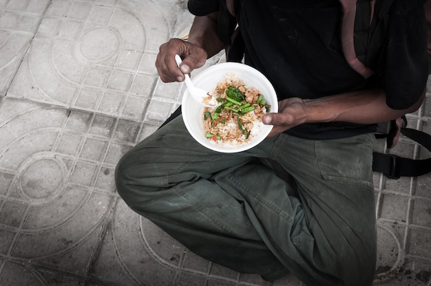 Poor man homeless with dirty hands eating food at street road floor
