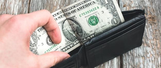 가난한 사람은 단 1달러로 빈 가죽 지갑을 열고 있습니다. 지갑에 돈이 없습니다. 빈곤과 실업. 오래 된 목조 소박한 배경입니다.