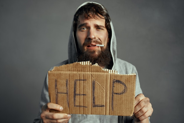 あごひげのサインを持つ貧しい男は、トランプのライフスタイルを助けます