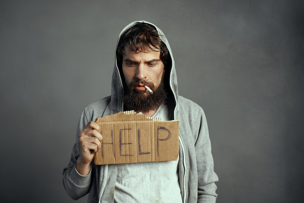 Poor man with a beard sign help the tramp lifestyle