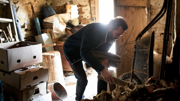 Poor mature man gathering firewood in shed at home, poverty concept.
