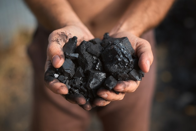 Poor middle-aged man holding the hands of stone coal for sale to provide food for his family