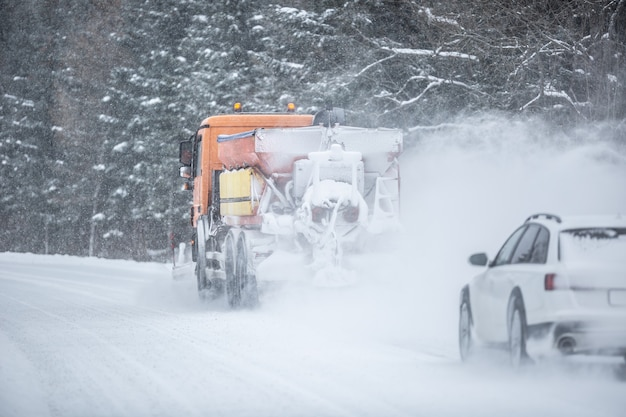 Poor road visibility of a car driving right behind a snow plow during winter road maintenance.