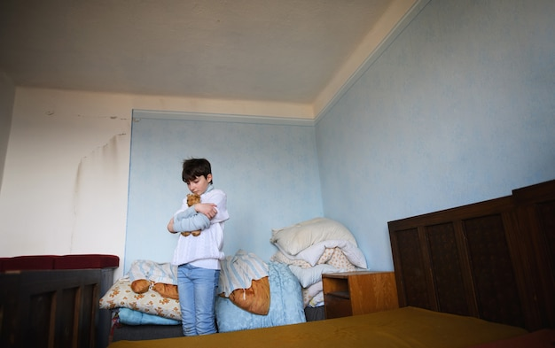 Poor sad small girl sitting in bedroom indoors at home, poverty concept.