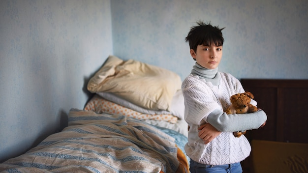 Poor sad small girl with teddy bear standing and looking at camera indoors at home, poverty concept.