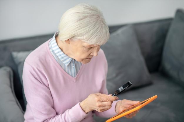 Плохое зрение. старшая женщина с лупой, читающая что-то на планшете