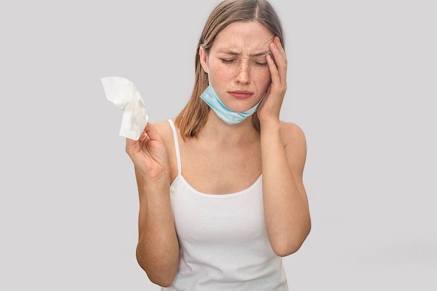 Poor young woman has headache. she holds hand on forehead and keeps eyes closed. mask in underneath chin. also she has napkin in roght hand.