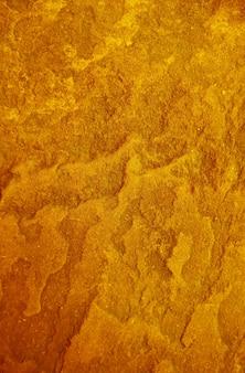 ポップアートスタイルのゴールドカラーのラフストーンの表面テクスチャ