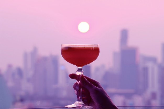 Pop art style pink and purple colored cocktail glass in hand with bright sun setting over the city