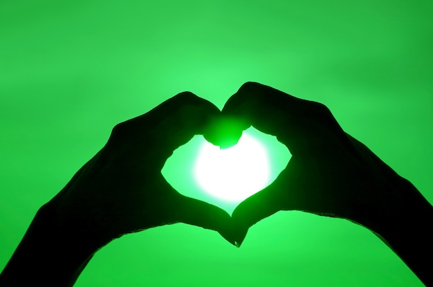 Pop art style silhouette of female's hand posing heart sign against shiny sun on green colored sky