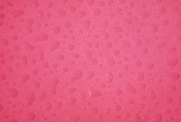 Pop art surreal style raspberry pink colored water droplets on the tabletop top view