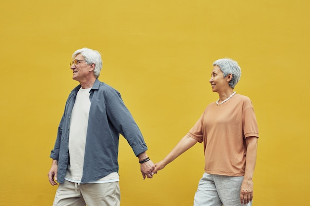 Pop color side view portrait of modern senior couple holding hands outdoors while walking against yellow background